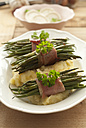 Plate of beans with raw ham and mashed potatoes on wooden table, close up - OD000068