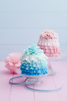 Pink and light blue mini cake on cake stand, close up - ECF000207