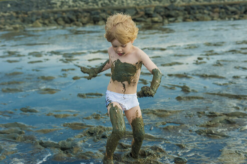 Germany, Schleswig Holstein, Boy playing in mud at beach - MJF000219