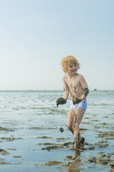 Germany, Schleswig Holstein, Boy playing in mud at beach - MJF000213