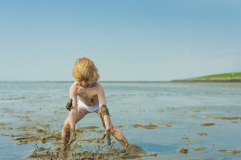 Germany, Schleswig Holstein, Boy playing in mud at beach - MJF000222