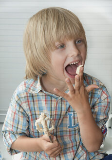 Austria, Boy licking cake dough, close up - CW000059