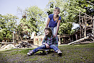 Germany, North Rhine Westphalia, Cologne, Mother and daughter playing with skateboard, smiling - FMKYF000398