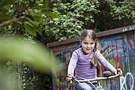 Germany, North Rhine Westphalia, Cologne, Girl riding bicycle in playground, smiling - FMKYF000448