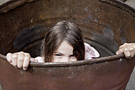 Germany, North Rhine Westphalia, Cologne, Girl in barrel at playground - FMKYF000375