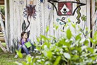 Germany, North Rhine Westphalia, Cologne, Girl sitting in playground - FMKYF000394