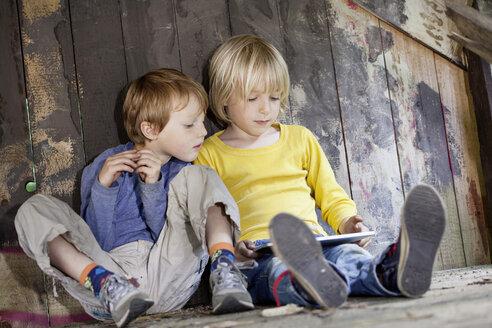 Germany, North Rhine Westphalia, Cologne, Boys using digital tablet in playground - FMKYF000427