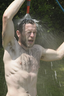 Germany, Baden Wuerttemberg, Young man taking shower in garden - LAF000084