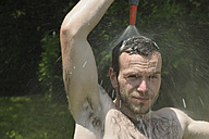 Germany, Baden Wuerttemberg, Portrait of young man taking shower in garden - LAF000083