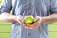 Mature man holding granny smith against green background, close up - MAEF006884