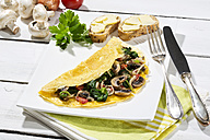 Omelette with mushrooms on wooden table - MAEF006895
