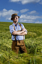 Germany, Bavaria, Farmer standing in field with arms crossed - MAEF006906