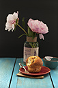 Sweet muffin on plate and peonies flowers in background - OD000171