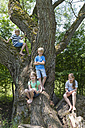 Germany, Bavaria, four children sitting on a tree at the urban forest - NH001373