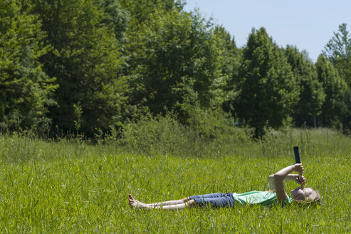 Germany, Bavaria, girl lying in gras and looking in the sky with binoculars - NH001380
