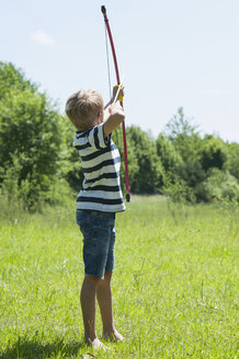 Germany, Bavaria, boy playing with bow and arrow - NH001383