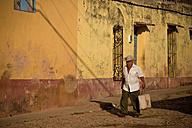 Cuba, Man walking on cobblestone street - PC000005