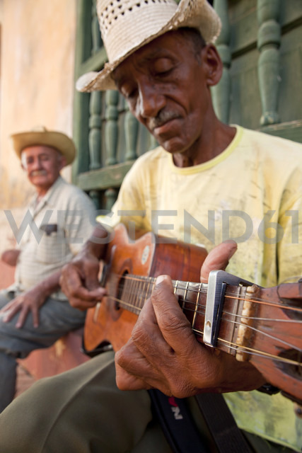 Cuba, Man playing guitar while another man sitting in background - PC000009