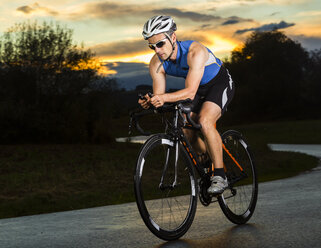 Germany, triathlete riding bicycle - STSF000058