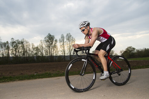 Germany, triathlete riding bicycle - STSF000050