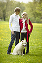 Germany, Young couple looking at each other with dog, smiling - DSCF000088