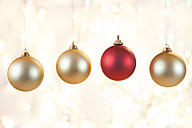Christmas baubles hanging in front shiny background, close up - SKF001331