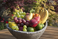 Germany, Rhineland Palatinate, Bowl of fruits on wooden table, close up - CSF019726