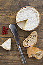 Camember cheese with red currant and baguette on wooden table - LVF000149
