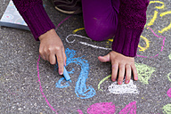 Germany, Girl drawing on street with chalk - SARF000048