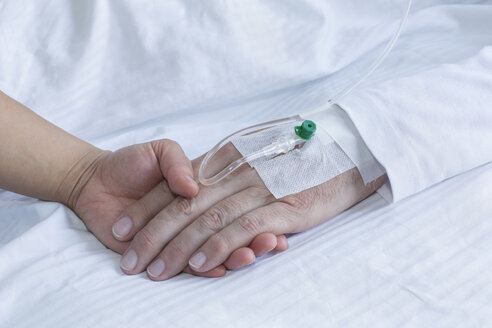 Germany, Freiburg, Woman holding hand of man in hospital, close up - DRF000022