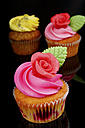 Cup cake with buttercream topping on black background, close up - HOHF000177