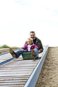 Germany, Kiel, Girl with her father playing with soapbox - JFE000149