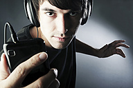 Germany, Cologne, Young man with headphones listening music from smart phone - JAT000110