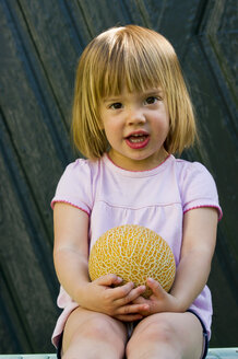 Germany, Bavaria, Portrait of girl holding galia melon, close up - LVF000154