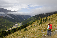 Italy, Alto Adige, Southern Tyrol, Sulden valley, View of hiker looking at view - LB000166