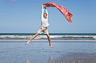 New Zealand, Mature woman jumping at Ninety Mile Beach - GW002313