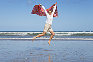 New Zealand, Mature woman jumping at Ninety Mile Beach - GW002315