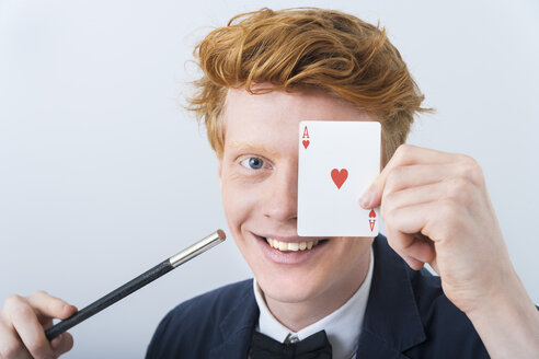 Portrait of young man showing magic of cards, smiling - TCF003473