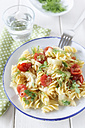 Plate of fennel tomato pasta on wooden table, close up - EVGF000145
