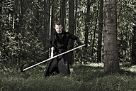 Germany, Bavaria, Mid adult man holding scythe in forest - MAE006982
