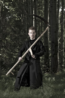 Germany, Bavaria, Mid adult man holding scythe in forest - MAE006983