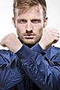 Portrait of mid adult man in blue jacket with arms crossed, close up - MAEF007002