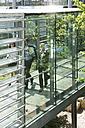 Germany, Hannover, Business people walking in office - KFF000104