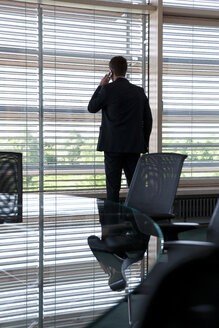 Businessman in office at the window - KFF000156