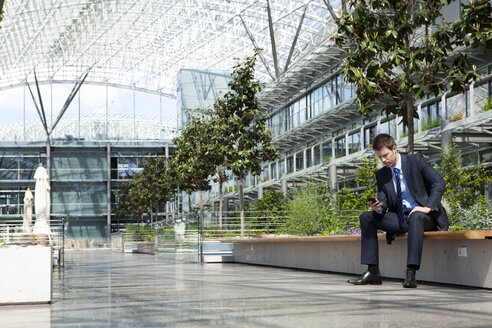 Businessman with cell phone in courtyard - KFF000120