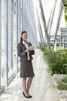 Smiling businesswoman holding digital tablet - KFF000159