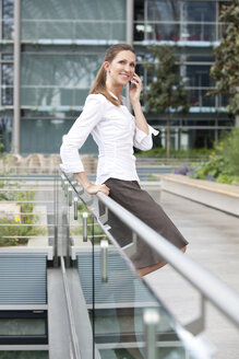 Businesswoman using cell phone on footbridge - KFF000165