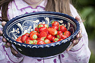 Germany, North Rhine Westphalia, Cologne, Girl holding bowl of strawberries, close up - FMKYF000502