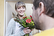 Germany, North Rhine Westphalia, Cologne, Young woman taking flowers from postman, smiling - FMKYF000481