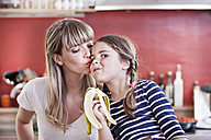 Germany, North Rhine Westphalia, Cologne, Girl eating banana while mother kissing - FMKYF000475